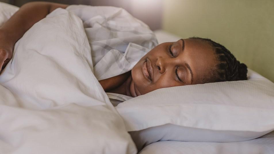woman asleep under weighted blanket
