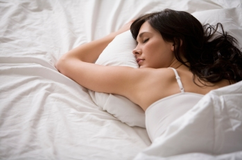 woman sleeping on her stomach on a bed of white linens