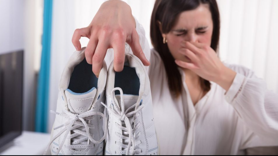 Woman Holding Dirty Smelling Shoes