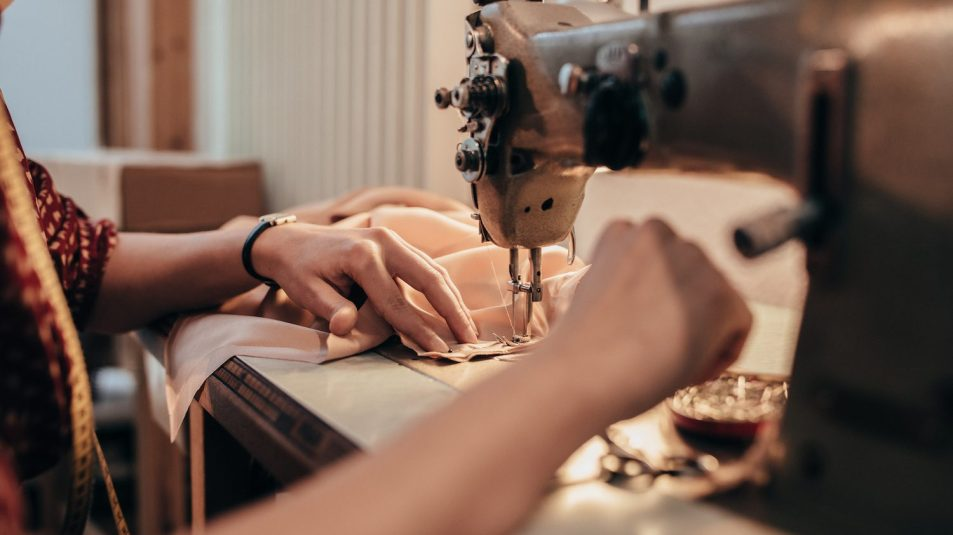 Tailor working with sewing machine, close-up.