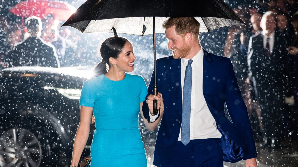 Prince Harry and Meghan smiling at each other under an umbrella