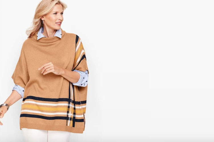woman wearing a golden poncho and turning her head to the side