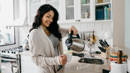 Woman pouring water from an electric kettle