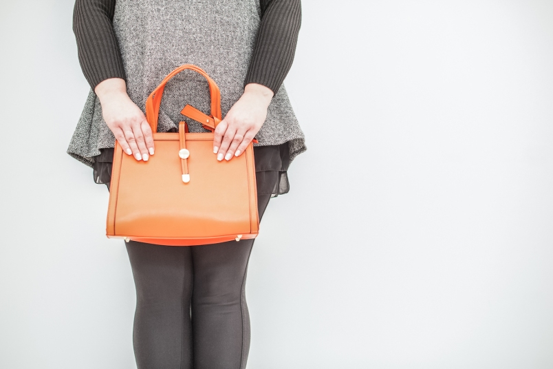 woman in a sweater dress and leggings holding an orange purse
