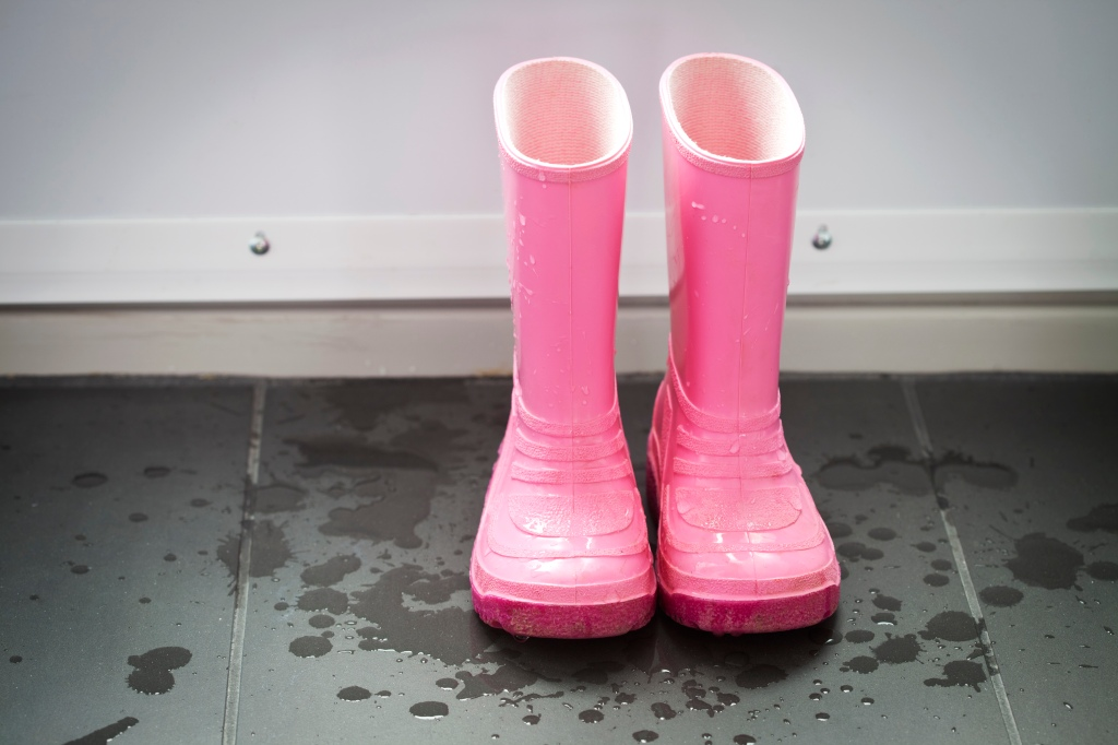A pair of wet pink galoshes in the entrance way.