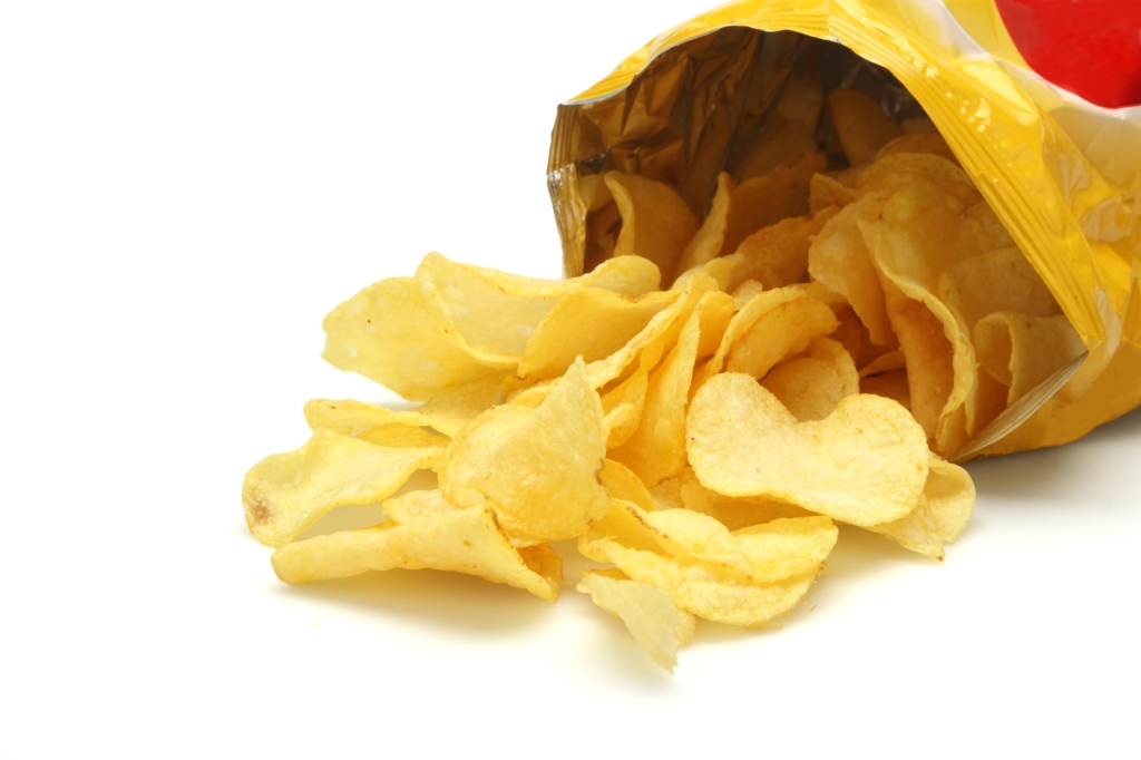 Bag of golden chips isolated on a white background.