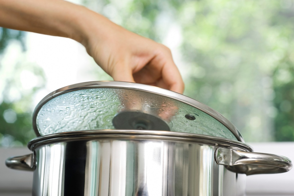 person removing lid from a pot