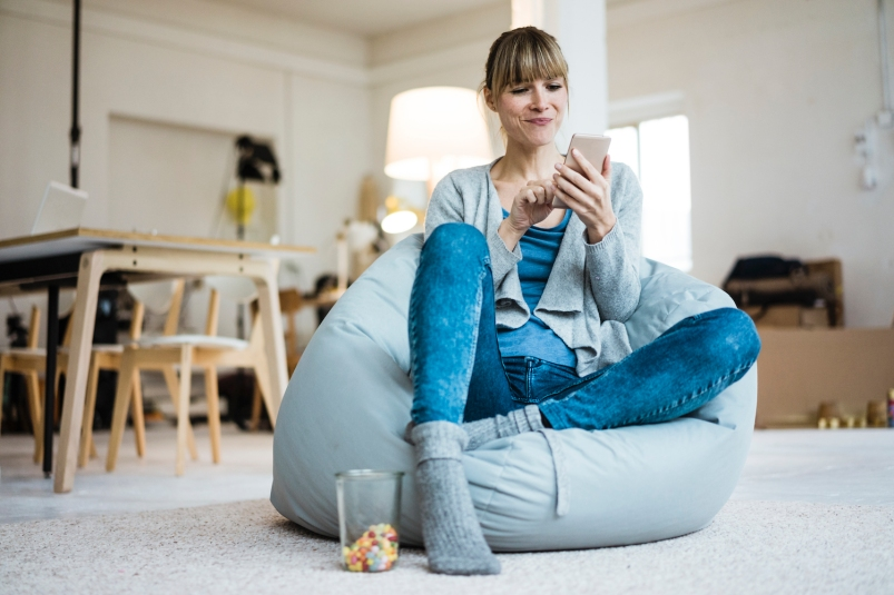 Smiling woman sitting in beanbag using cell phone