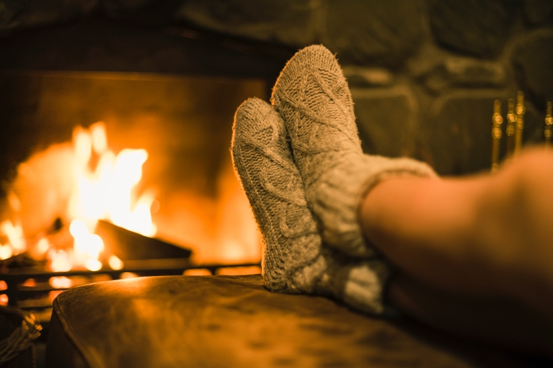 a pair of sock-clad feet propped up in front of a fireplace