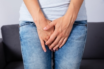 woman struggling with urinary incontinence holding her crotch