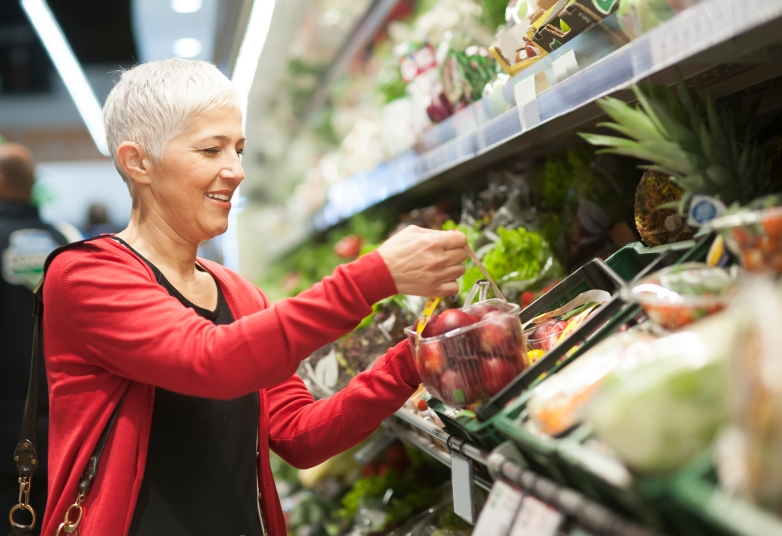 woman shopping at market in produce aisle