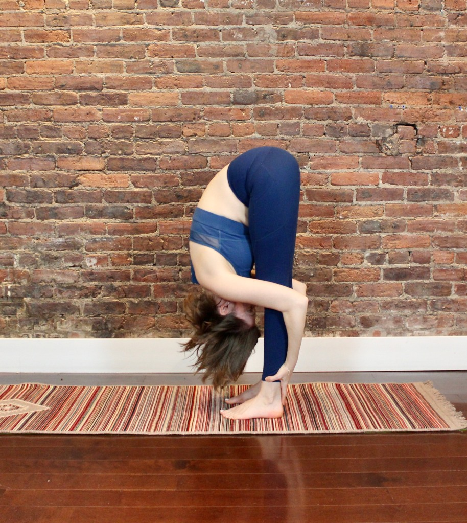 woman folding forward over her legs