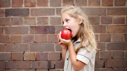 Little girl biting into apple