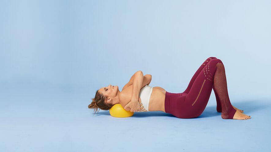 woman hugging herself laying on ball