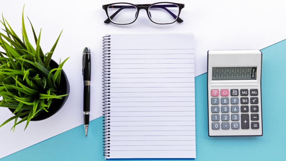 A blank journal, pen, glasses, calculator, and plant