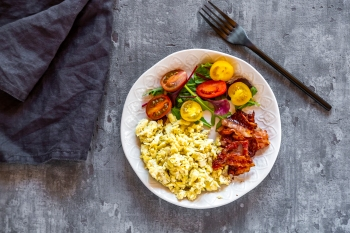 Scrambled eggs with fried bacon and salad with tomato, low carb, from above