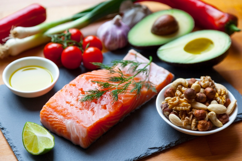 Table top still life of foods high in healthy fats such as Salmon, olive oil, nuts and avocados with vegetables and herbs.