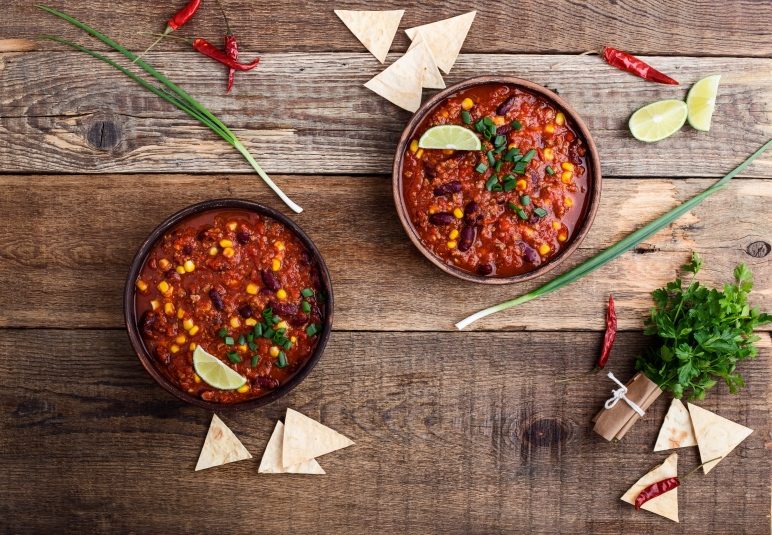 Chili con carne stew served in ceramic bowll on rustic wooden table viewed from above, Mexican cuisine