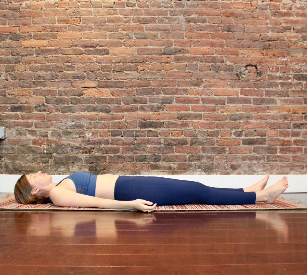 woman lying flat on the ground in yoga