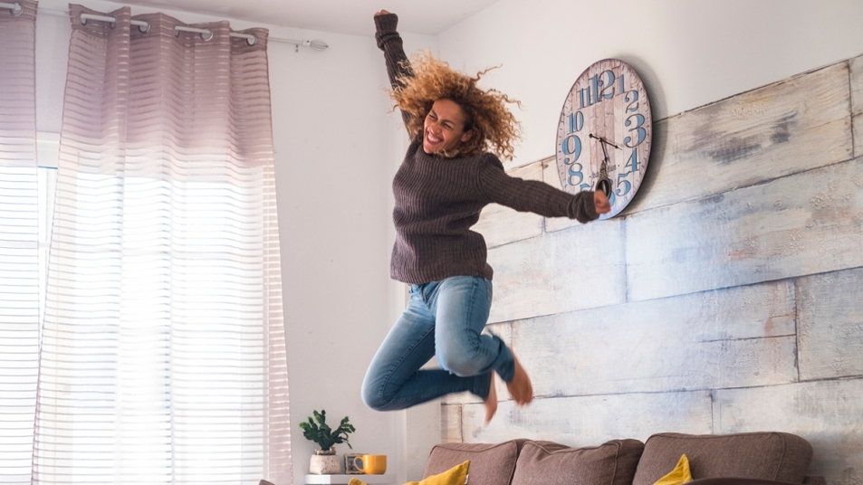 Woman jumping on living room couch