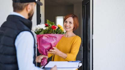 Man courier delivering bouquet of flowers to a young woman.