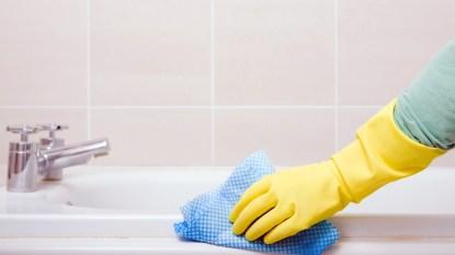 Gloved hand scrubbing bath tub
