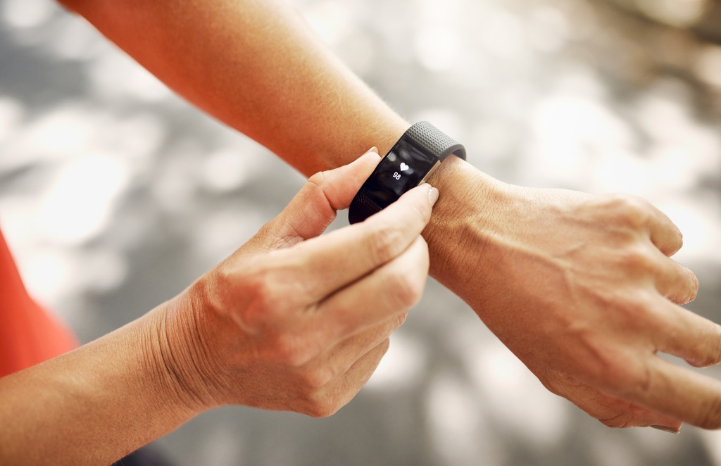 Woman checking fitness tracker on wrist