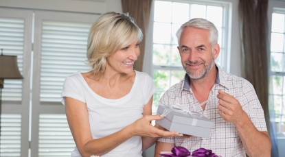 Happy woman giving a gift box to smiling mature man at home