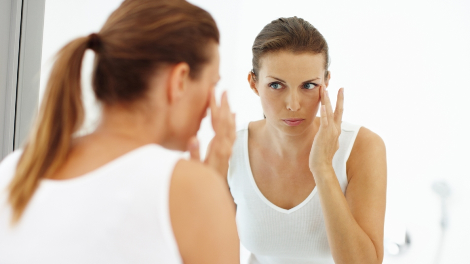 Woman looking at eyes in mirror