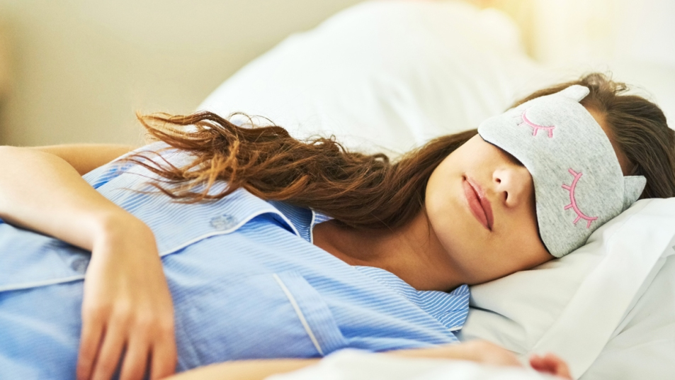Woman in bed with sleep mask