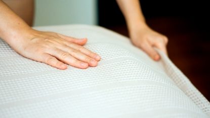 Hands smoothing out bed sheets
