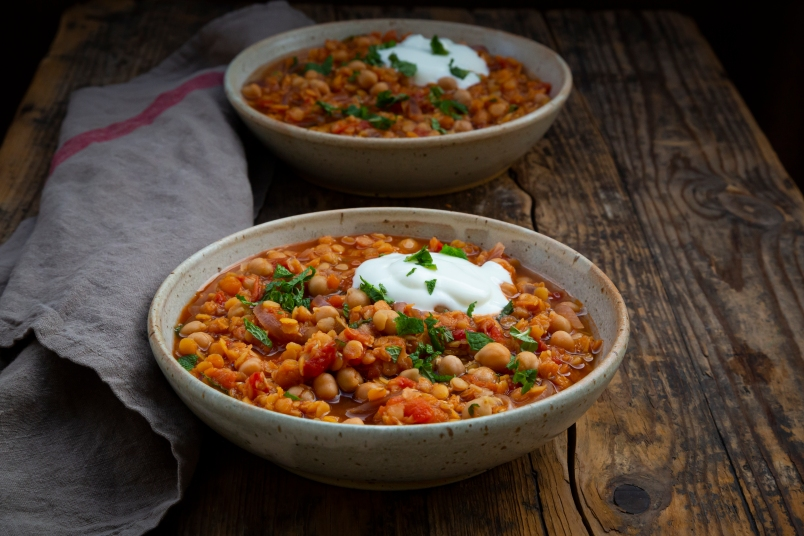 two bowls of red lentil soup with chickpeas