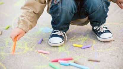 Little boy drawing on sidewalk with chalk