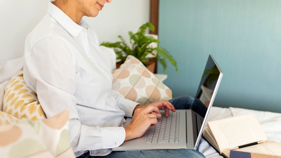 woman working on laptop in bed