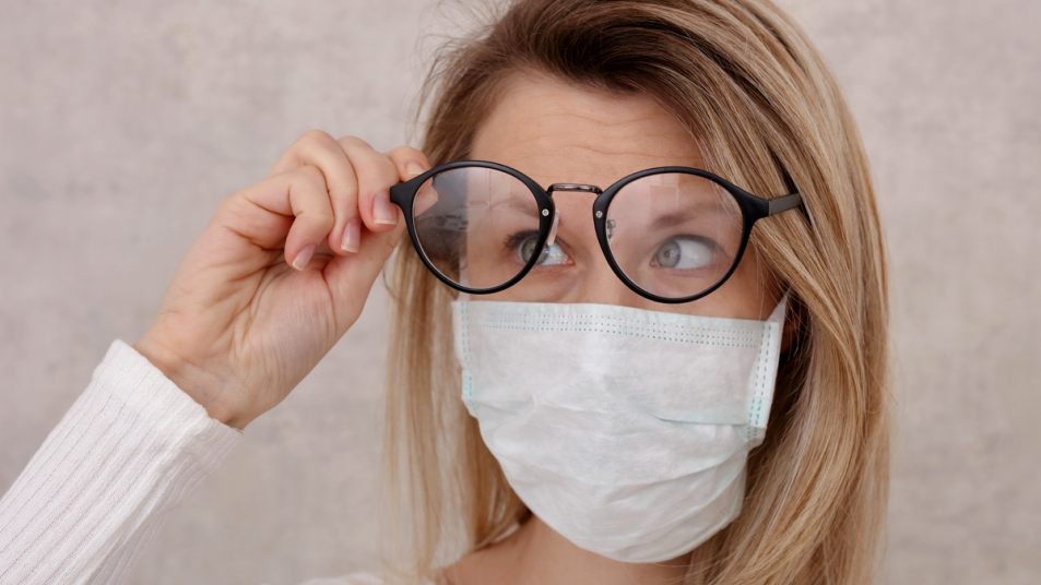 Woman lifting eye glasses while wearing a face mask