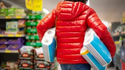 Woman at store with several rolls of toilet paper