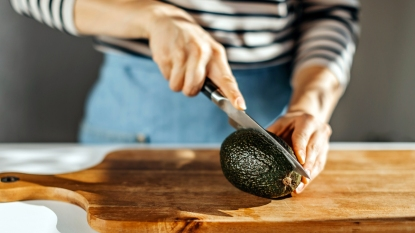 Woman slicing into avocado