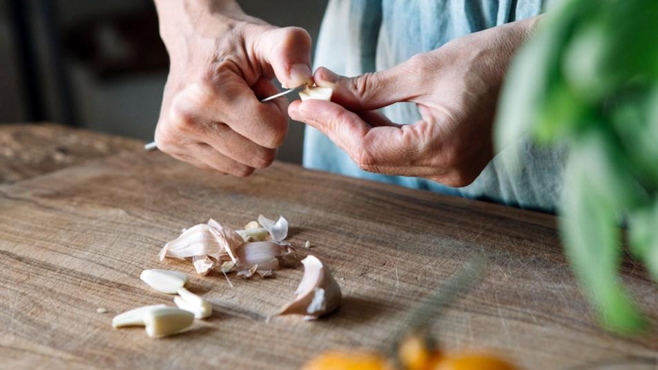 Woman peeling garlic with knife