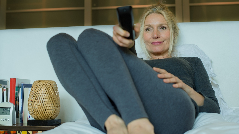 Woman watching TV in bed
