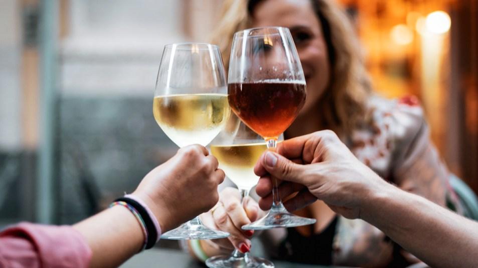 Group of people cheers-ing glasses of wine
