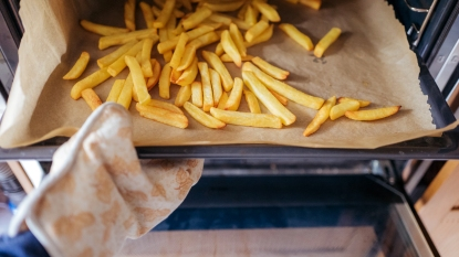Hand taking fries out of the oven