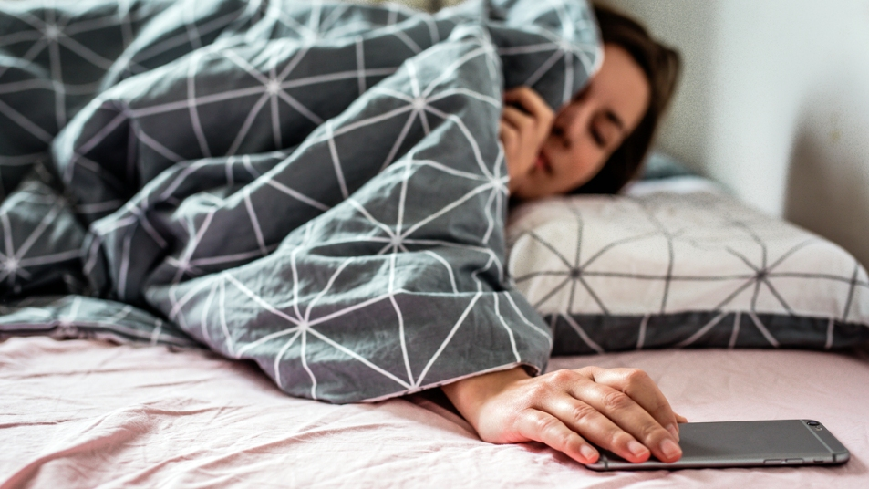 Woman under bed covers reaching for her phone