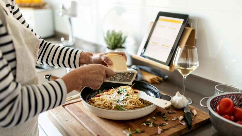 Woman cooking with laptop open