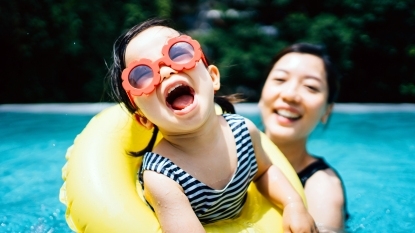 Toddler in sunglasses smiling with mom in pool