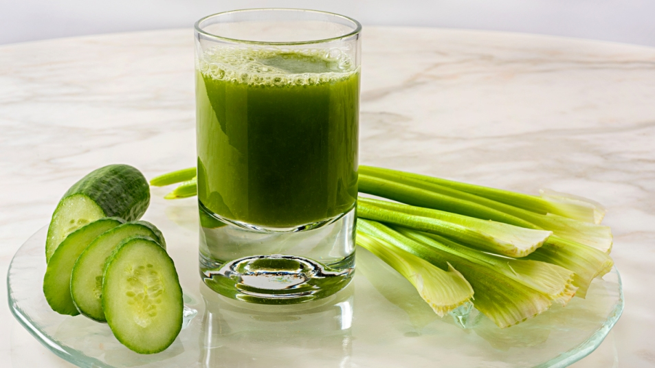 Celery and cucumbers around glass of green juice