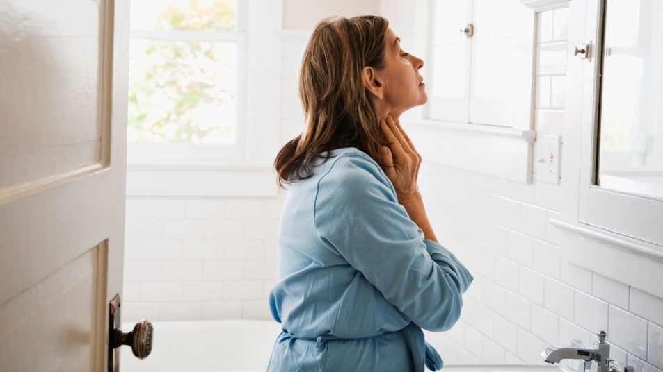Woman looking at her neck in the mirror