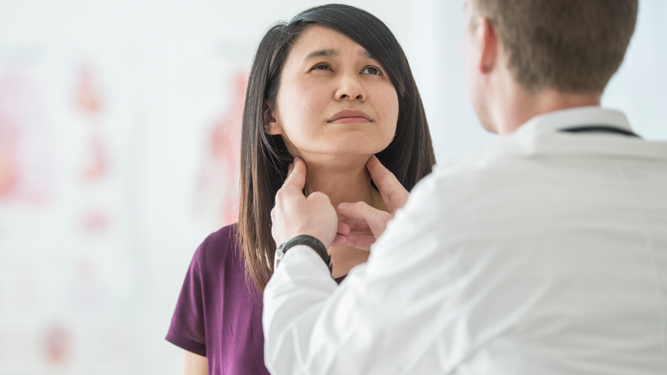 Doctor checking woman's thyroid glands