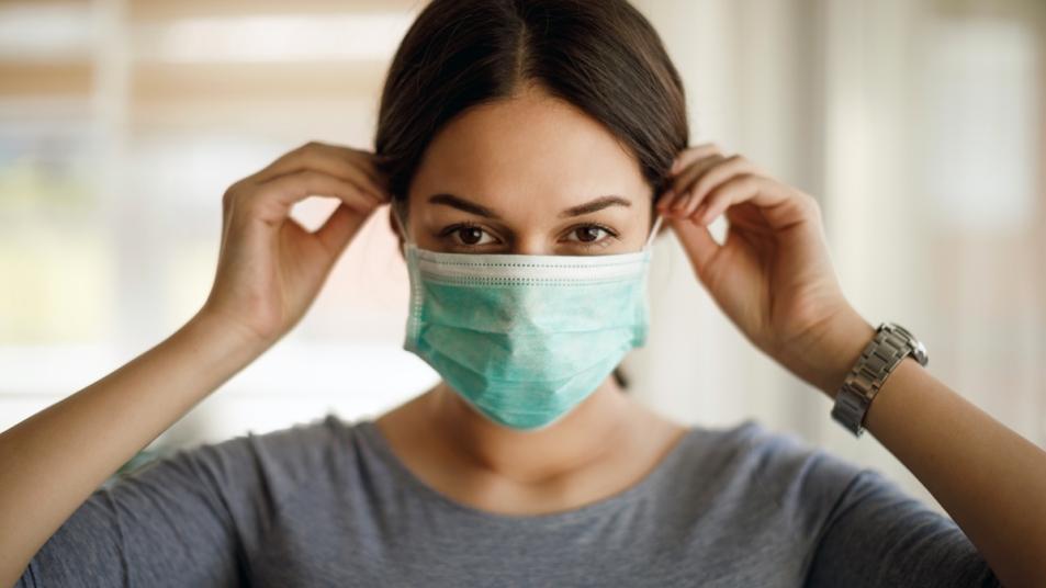 Woman with brown hair putting on a surgical face mask