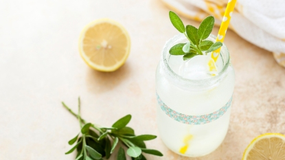 Glass jar of lemonade with sage sprigs and yellow paper straw