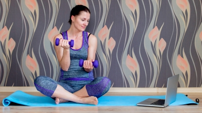 Woman sitting on a yoga mat using weights and looking at laptop